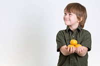 Boy holding tangerines in his hands
