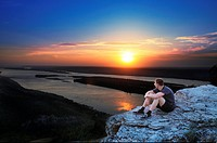 Boy watches sunset skies in Russian National Park sitting on a steep rock of Zhiguli mountains