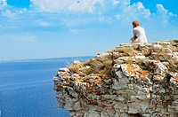 Girl sitting on a rock of Devia hill and observing Volga reservoir in Russian National Park 'Samara Luka'