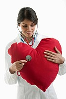 Doctor with stethoscope on heart pillow