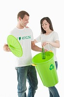 Couple throwing glass bottle in the recycling bin (thumbnail)