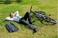 Businessman lying down in grass next to bicycle enjoying the sun