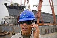 Ship yard foreman speaks on cellular telephone, Aotai Ship Manufacturing Company, Yueqing, Zhejiang Province, China