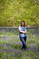 A young woman standing in the woods, holding a bunch of bluebells, smiling