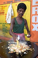 Man cooking South Indian style scrambled eggs at a roadside dhaba in Pondicherry India.