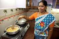 Indian woman cooking meat stew.
