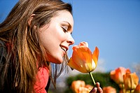 A young woman smelling a tulip, close_up