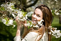 A young woman holding a branch of spring blossom