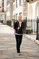 A mid adult woman carrying a yoga mat, walking (thumbnail)