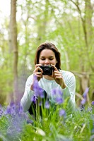 A young woman photographing bluebells (thumbnail)