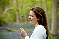 Portrait of a young woman holding a bluebell