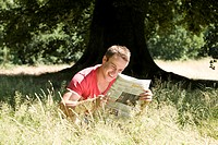 A young man sitting on the grass, reading a newspaper