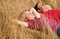 A young couple lying side by side in the sun