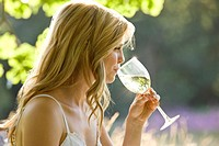 A young woman drinking a glass of white wine (thumbnail)