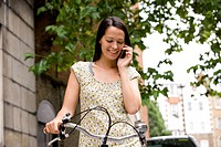 A young woman standing with her bicycle, speaking on a mobile phone
