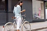 A young woman on a bicycle, using her mobile phone