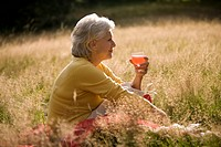 A senior woman holding a glass of juice