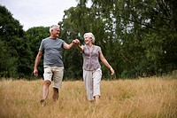 A senior couple walking through a field, holding hands (thumbnail)