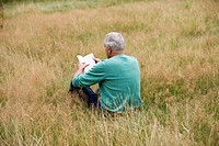 A senior man sitting on the grass, reading a book, rear view