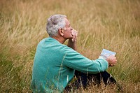 A senior man sitting on the grass, holding a book, looking thoughtful (thumbnail)