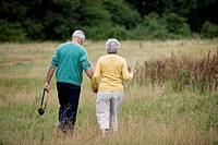 A senior couple walking through a field, carrying a camera