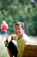 A middle aged man sitting on the grass, drinking a bottle of beer