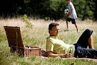A middle aged man lying on the grass, having a beer