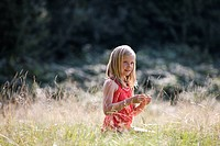 A young girl sitting in long grass, smiling