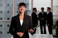 Indian woman standing in foreground smiling with male colleagues in background
