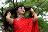 Indian woman wearing red sari smiling with hands in hair