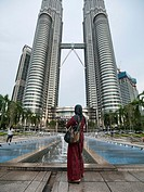 Malaysian woman standing in front of the Petronas Towers in Kuala Lumpur, Malaysia