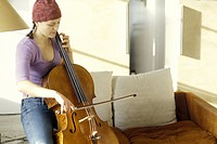 Side view of a woman playing a cello.