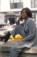 Profile of a businesswoman talking on her cell phone.