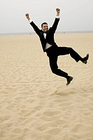 Groom jumping in joy at beach.