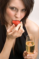 Woman holding a flute of champagne and strawberry