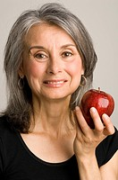 Studio shot of mature woman holding a red apple