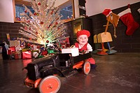 Infant girl wearing red hat playing with vintage truck on living room floor with Christmas decorations in background winter Alaska