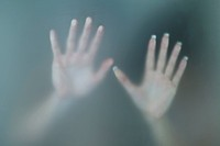 hands of woman in shower touching glass door