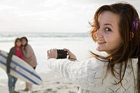 Teenage girl taking photograph of two friends with surfboard