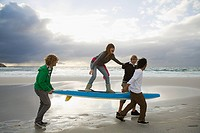 Young people carrying surfboard, person balancing on top (thumbnail)