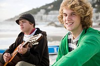 Boys playing guitar on beach