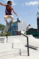 Skateboarder jumping over a rail