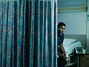 Male nurse behind hospital curtain