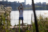 Male runner stretching by river
