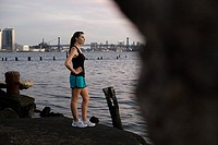 Runner standing by river in brooklyn