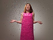 Young girl wearing pink dress with ticker tape, portrait
