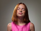 Young girl wearing pink dress with eyes closed, portrait