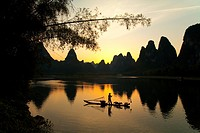 Chinese fisherman on bamboo raft fishing with cormorants at sunset on Li River, Guilin, Guangxi Province, China