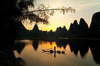 Chinese fisherman on bamboo raft fishing with cormorants at sunset on Li River, Guilin, Guangxi Province, China