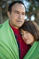 Mature couple sharing blanket outdoors, portrait